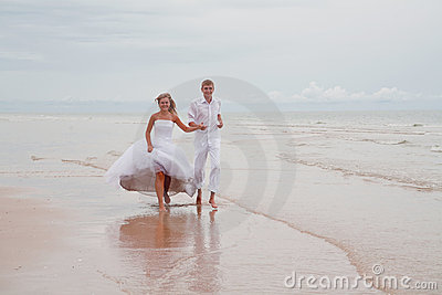 Couple running down a beach