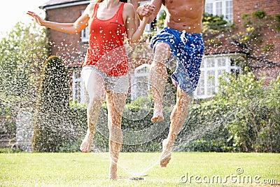 Couple Running Through Garden Sprinkler