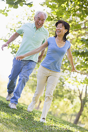 Couple running outdoors in park smiling