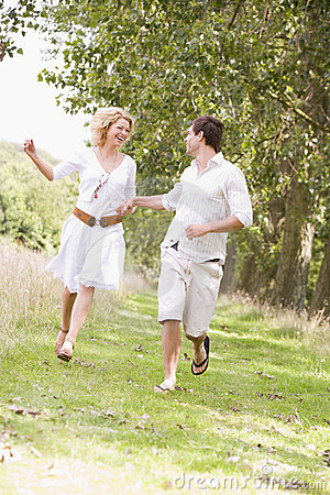 Couple running on path holding hands and smiling