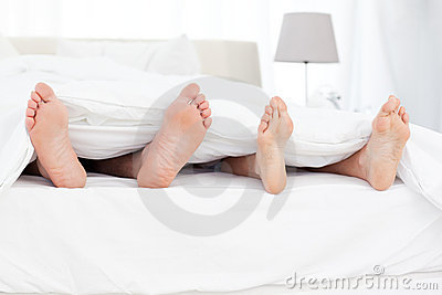 Couple s feet in the bed