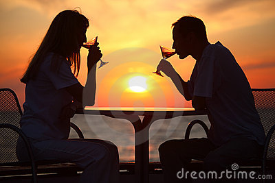 Couple s silhouettes on sunset behind table