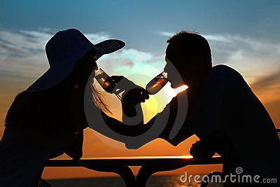 Couple s silhouettes on sunset drink from glasses