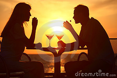 Couple s silhouettes on sunset sit at table