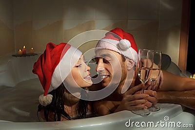 Couple in santa hats is enjoying a bath