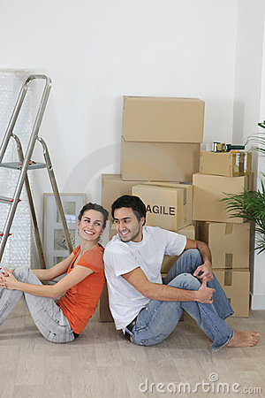 Couple sat next to boxes