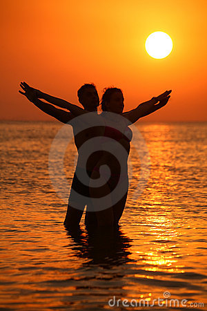 Couple in sea on sunset with hands as wings