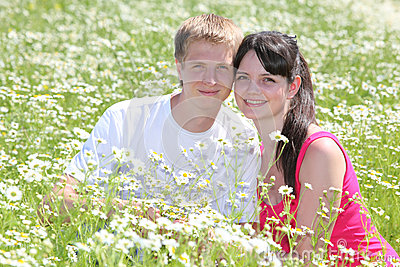 Couple seat in camomile field
