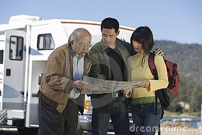 Couple and senior father reading map outside RV