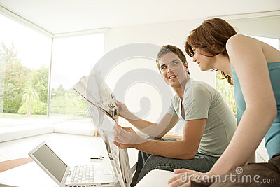 Couple Sharing Newspaper at Home