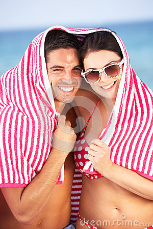 Couple Sheltering From Sun On Beach Holiday