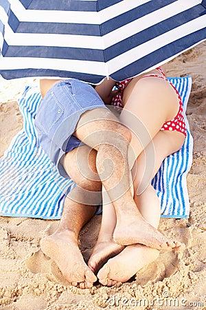 Couple Sheltering From Sun Under Beach Umbrella