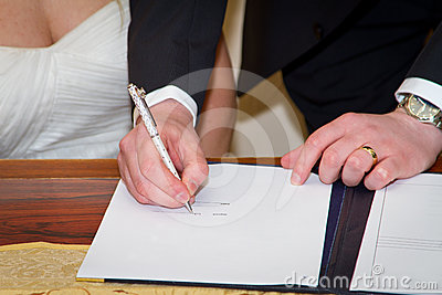 Couple signing marriage registration form