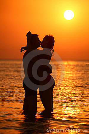 Couple silhouette embraces and kisses on sunset