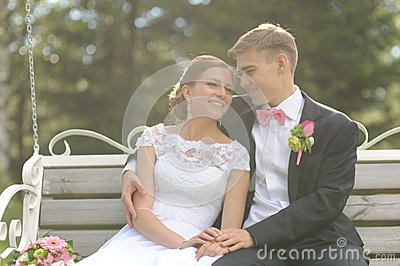 Couple sit on bench in park