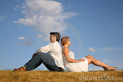 Couple sit on meadow