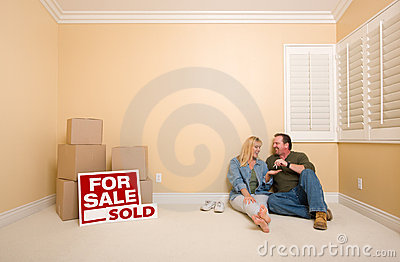 Couple Sit Near Boxes and Sold Real Estate Signs