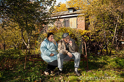 Couple sit on old rusty bed in autumnal garden