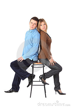 Couple sits on bar stool back to back