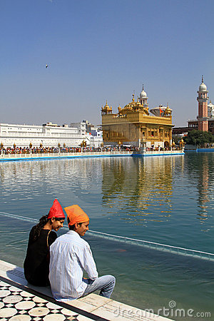 Couple sitting against golden temple Editorial Stock Image