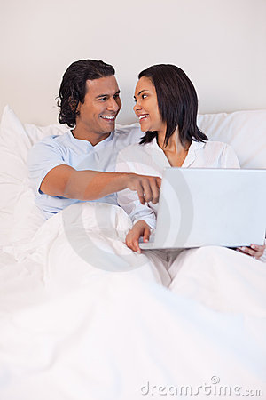 Couple sitting on the bed surfing the internet
