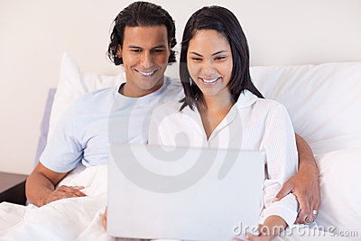 Couple sitting on the bed with their laptop