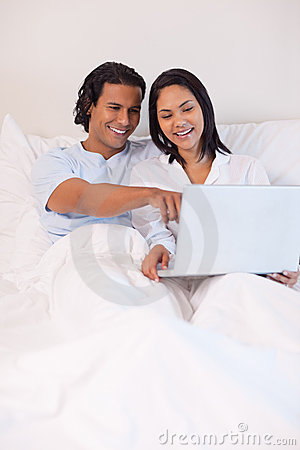 Couple sitting on the bed with their notebook