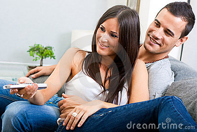 Couple sitting on couch and watching television to