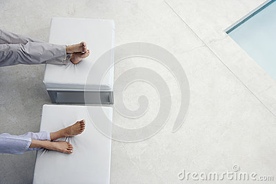 Couple Sitting With Feet On Foot Stools