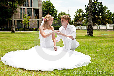 Couple sitting on grass in a tropical park