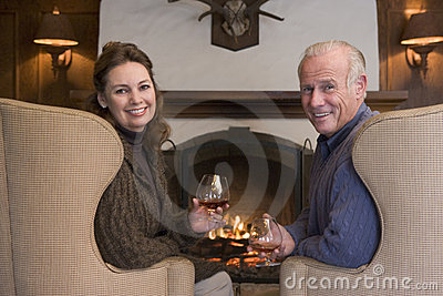 Couple sitting in living room by fireplace