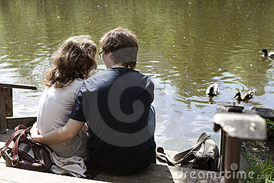 A couple sitting near river