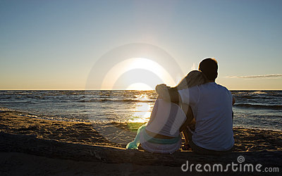 Couple sitting near the sea on sunset