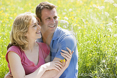Couple sitting outdoors holding flower smiling