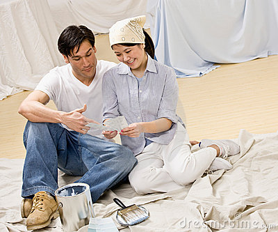 Couple sitting with paint can and color swatch