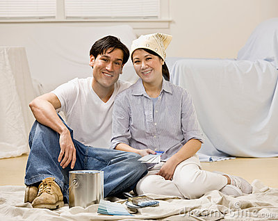 Couple sitting with paint can and paint swatch