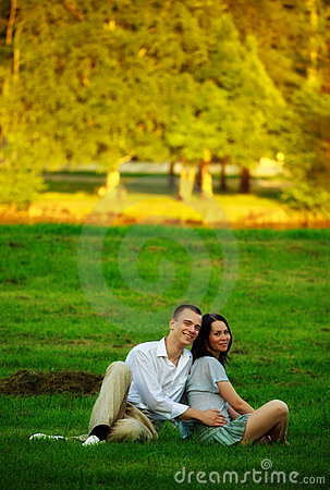 Couple sitting on park lawn