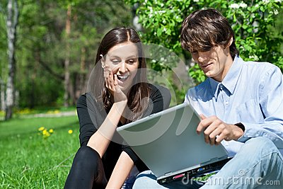 Couple sitting in park and using laptop