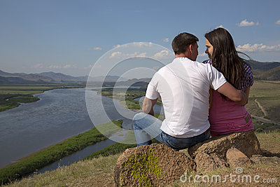 Couple sitting on a rock in mountains