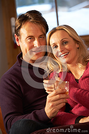 Couple Sitting On Sofa With Glasses Of Whisky