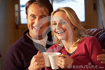 Couple Sitting On Sofa With Hot Drinks Watching TV