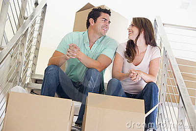 Couple sitting on staircase with boxes in new home