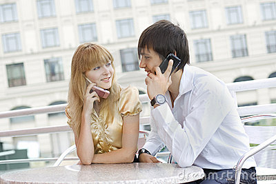 Couple sitting at table using their cell phones