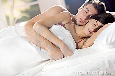 Couple sleeping and hugging on the bed