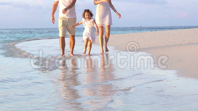 A couple with a small child walking a beach. Slow motion. A couple with a small child walking the beach. Slow motion stock footage
