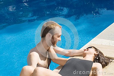 Couple Smiling Near and in Pool - horizontal