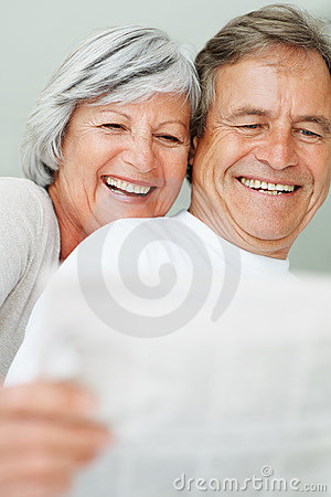 Couple smiling together while reading newspaper
