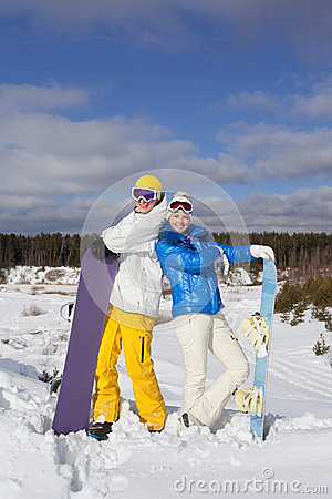 Couple with snowboards in their hand standing on a hillside