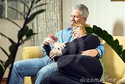 A Couple Snuggling on A Couch Together-Vertical