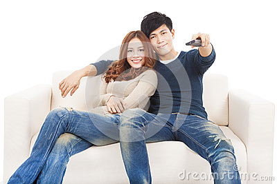 Couple on sofa watching TV with remote control